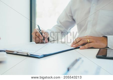 Signing a car insurance policy the agent is holding the document