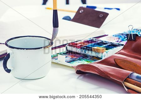 Close-up of the artist draws a wooden brush and watercolors in the album for drawing on the table lie a drawing pallet a leather case with brushes a metal mug with water a side view