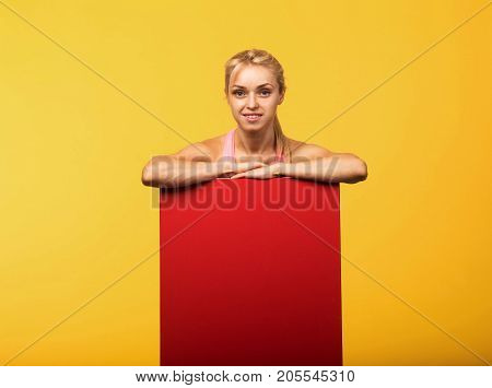 Young  confident woman portrait of a businesswoman showing presentation, pointing placard yellow background. Ideal for banners, registration forms, presentation, landings, presenting concept.