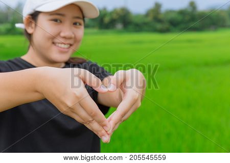 love healthy concept Asian teen show hand heart sign of love in the park