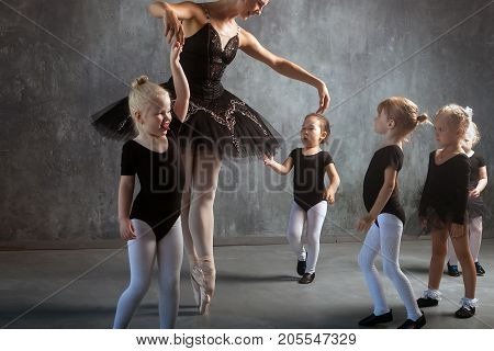 A beautiful blonde woman in a black dance tutu white pantyhose and pointe shoes is dancing and teaches young girls to dance ballet in a dark studio