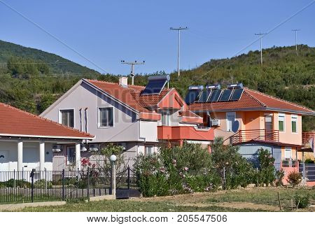 Solar panels on the roofs of new houses in the village and clear sky