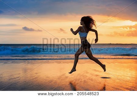 Barefoot sporty girl silhouette running along ocean surf by water pool to keep fit and health. Sunset black beach background with sun. Woman fitness jogging sport activity on summer family holiday.