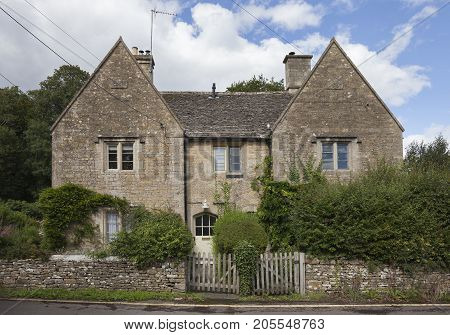 Stone semi-detached cottages in Lower Slaughter village Gloucestershire England.