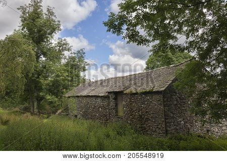 Traditional stone barn on the banks of Ullswater the Lake District Cumbria England.