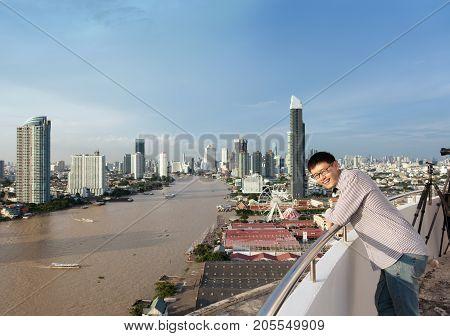 Asian Man With Chao Phraya River At Noon In Bangkok, Thailand