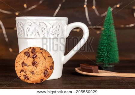 A photo of a cookie with a cup of hot chocolate behind it, with a little Christmas tree, and fairy lights in the blurred background, side view, on dark textures