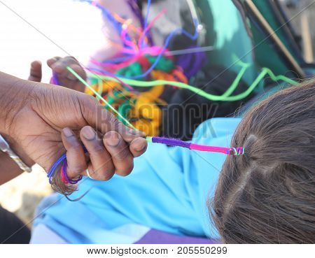 African Woman Creates A Hairstyle With A Colorful Braid In The H
