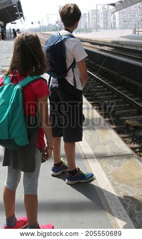 young brother and his little sister with backpacks waiting for the train during their trip