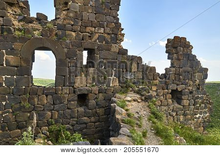 Ruined wall of the medieval armenian fortress Amberd with loopholes and windows