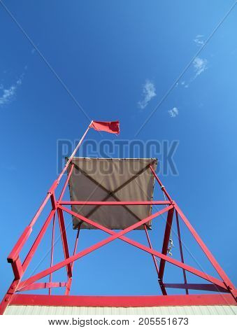High Turret Of Lifeguard On The Beach With The Red Flag