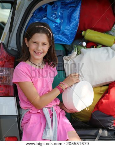 little girl loads the bags in the trunk of her car before leaving for the holidays