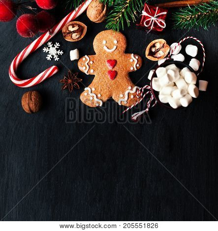 Christmas composition with Christmas gift gingerbread man cookie fir tree branches xmas holiday decorations and festive symbols on black background with copy space for your design or Merry Christmas text