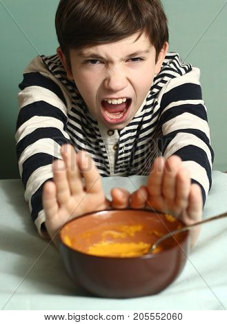 Preteen Boy With Disgust Grimace Refuse Eating Pumpking Soup