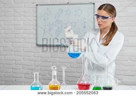 The scientist works with the chemical liquids in the laboratory. She wears protective chemical glasswere and white uniform. Analyzing formulas and using colorful bottles , woman makes an experiment.