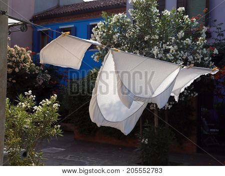 White bed sheets spread to dry in the sun in a city in the mediterranean area