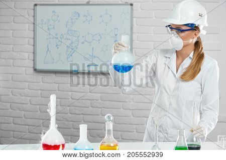 Using formulas and working with smoky chemical liquids in the tubes, scientist makes the chemical experiment in the lab. She wears white protective uniform, helmet, chemical facemask and gloves.