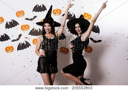 Two models are posing, lifting their left arms up and holding the glasses in the right with wine. They are dressed in black sexy witch suits and smile