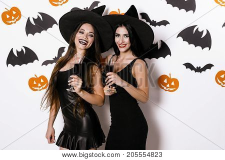 Two sexy models in black tight dresses and witch hats smile and posing against the background of bats with glasses of wine in their hands