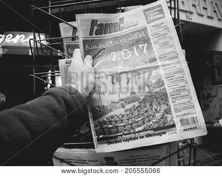 PARIS FRANCE - SEP 25 2017: Man buying latest L'Ami Hebdo French newspaper with portrait of Angela Merkel after election in Germany for the Chancellor of Germany the head of the federal government - black and white