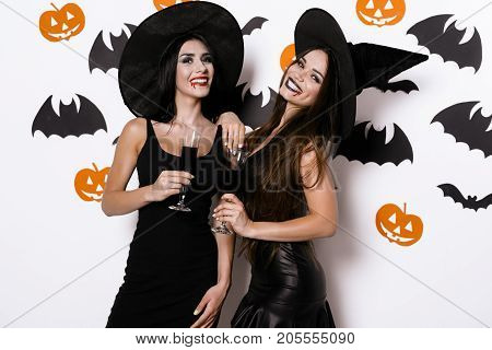 Halloween party. Two sexy vampires in witch hats and black tight dresses are posing with glasses of blood in their hands.