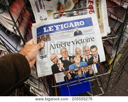 PARIS FRANCE - SEP 25 2017: Man buying latest Le Figaro with Bitter Vitory message about Angela Merkel winning election in Germany for the Chancellor of Germany the head of the federal government