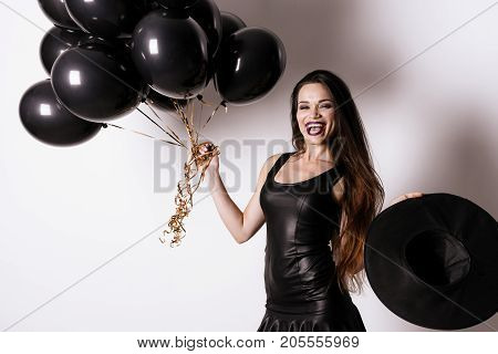 The dark-haired model in a black tight dress is posing with black balloons in one hand and a black witch hat in the other. She laughs