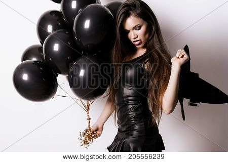 Super sexy. A girl in a black and sexy dress poses with black balloons in her hand, holding a witch hat in the other hand. She looks down coquettishly.