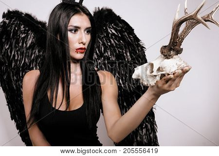 The demon girl. The black-haired model in a black dress and with black wings behind her pensively looks at the deer skull she holds in her hands