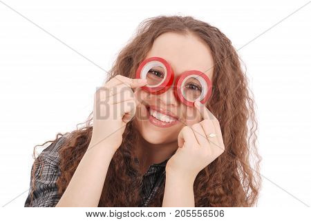 Portrait of a funny young girl looking at camera through insulating tape isolated on a white background