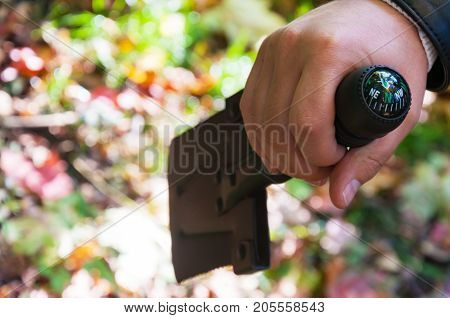 A Small Shovel That Holds A Man's Hand And A Forest. A Compass Is Located On The Shovel Handle. The