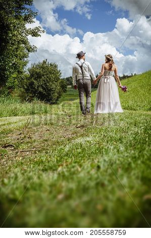Photo of a young newlywed couple walking down a path through a park holding hands.