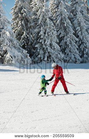 Ski Trainer Helping Little Boy, Color Image, Two People