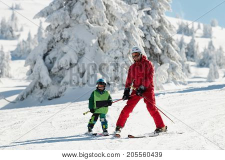 Ski Instructor Teaching Little Boy Skiing, Color Image, Two People