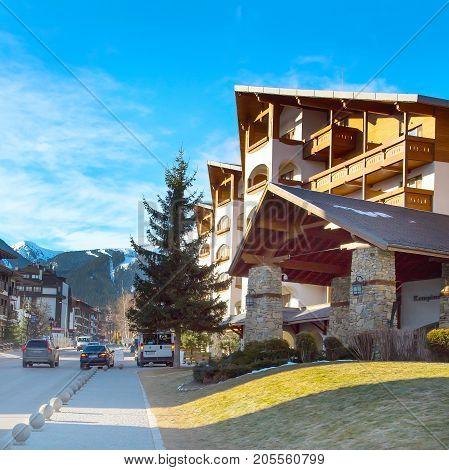 Bansko, Bulgaria - February 19, 2015: Kempinski Hotel, street and mountain ski slopes view in Bansko, Bulgaria