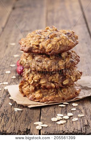 Applesauce oatmeal cookies with dried cranberries on wooden table.