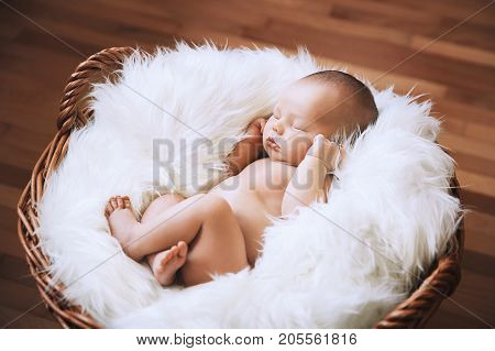 Sleeping newborn baby in a wrap on white blanket. Beautiful portrait of little child girl 7 days one week old.