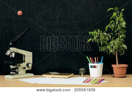 Teacher or student desk table. Education background. Education mockup concept. Microscope book calculator green plant tree scattered colour pencils and page paper on blackboard background.