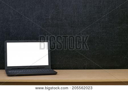 Teacher or student desk table. Education background. Education mockup concept. Laptop computer with blank screen on blackboard (chalkboard) background.