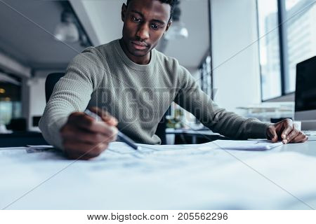 Businessman pointing at building plan in office. Black man working on construction plan.