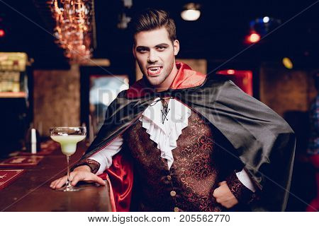 Halloween party. The guy in the cloak and suit of Count Dracula poses near the bar run-off in a nightclub. Next to him is a glass with an alcoholic cocktail