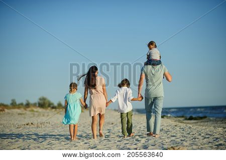 Big happy family walking at the beach. Mom dad and three children. The blue sky the sun fresh sea wind. Pleasure from nature and communication. Back view. poster