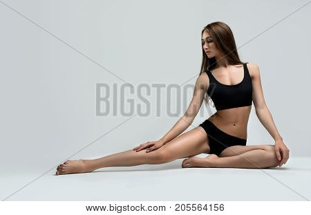Slim brunette her hair loose wearing black sporty top and tanga sitting on the floor on gray background