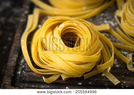 Fresh homemade pasta tagliatelle at wooden table. Close up selective focus.