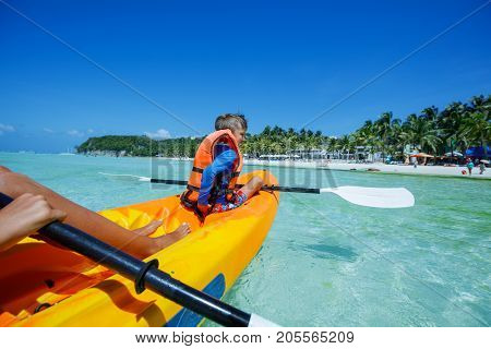 Back view of boy kayaking at tropical sea on yellow kayak