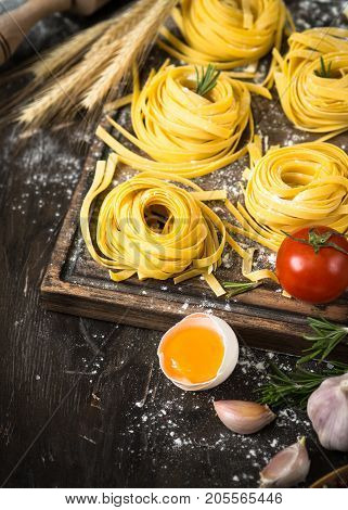 Preparation italian pasta tagliatelle at dark wooden table. Italian food background.