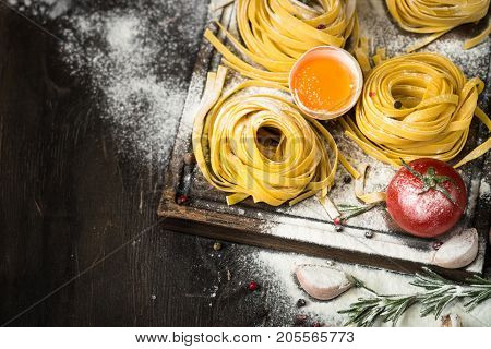 Preparation pasta tagliatelle and ingredients for cooking at dark wooden table. Italian food background.