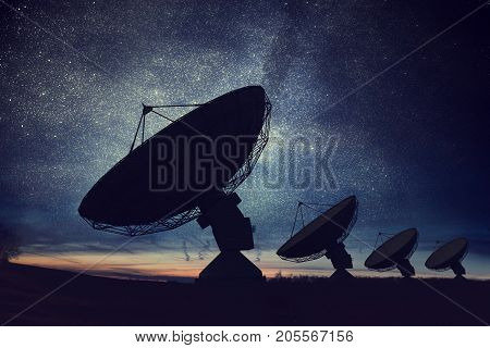 Silhouettes Of Satellite Dishes Or Radio Antennas Against Night