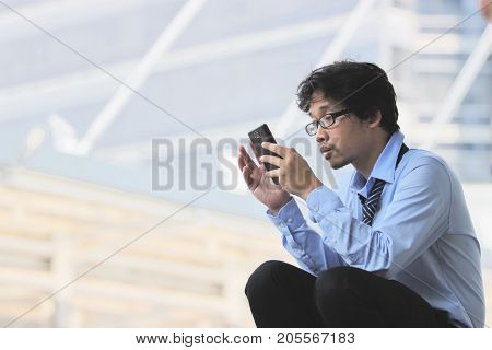 Side view of young unemployed Asian man finding job with mobile smart phone at blurred city background.