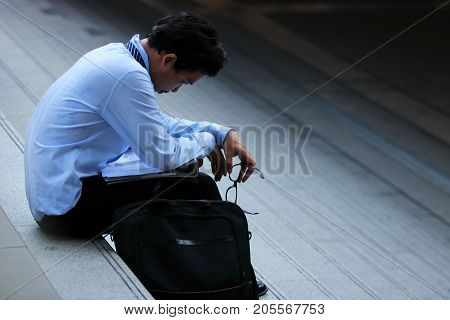 Side view of stressed frustrated young Asian man sitting on stairway. he feeling disappointed or tired with something.